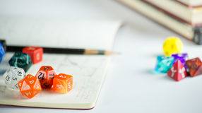Dice with Pencils and a Notebook. Multicolored dice with Pencils, notebook, and books in background Stock Photography