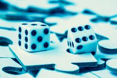 Dice on the pile of jigsaw puzzles stock photo