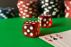 Dice, poker chips and playing cards on the green table . Game co royalty free stock images