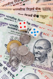 Dice and rupee coins on Indian rupee notes Stock Photo