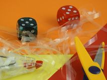 Dice scissors tape-eraser on a orange red a nd yellow colorful table royalty free stock images