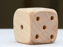 Dice. Single wooden die on a white table stock images