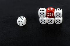 Dice six units and a red six on a black background royalty free stock photo
