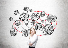 Dice sketch game theory. Thoughtful businesswoman standing against concrete wall with connected dice sketch. Game and probability theory royalty free stock photos