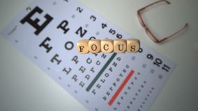 Dice spelling out focus falling onto eye test beside glasses Stock Photos