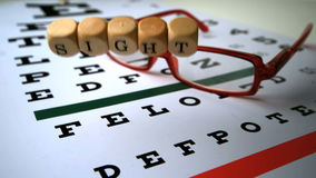 Dice spelling out sight falling onto eye test next to glasses stock footage
