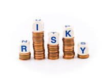 Dice Spelling Risky on Penny Stacks. Letter Dice Spelling Risky atop Penny Stacks Stock Photography