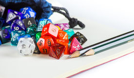 Dice spilling out of a Dice bag with Pencils. Multicolored dice spilling out of a Dice bag with Pencils and a notebook Royalty Free Stock Images
