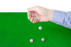 Dice thrown from male hand on table with green cloth Royalty Free Stock Images