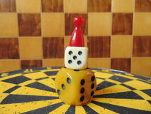 Dice tower with play figure on top with chess board background Stock Photography