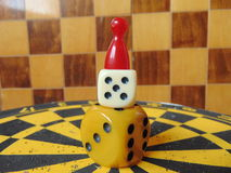 Dice tower with play figure on top with chess board background Royalty Free Stock Photo