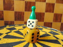 Dice tower with play figure on top with chess board background. Dice tower with play figure on top on dartboard Stock Photos
