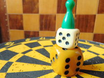 Dice tower with play figure on top with chess board background. Dice tower with play figure on top on dartboard stock photography