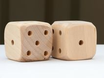 Dice. Two wooden dice on a white table stock photos