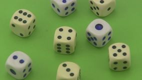 Dice that are used in board games and for gambling rotating on a green background. stock video