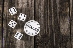 Dice on Vintage Wood Table - Casino Dealer Chip stock images
