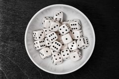 Dice in a white bowl on  black board stock photos