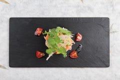 Diced三文鱼沙拉顶视图用鲕梨、蕃茄、葱、辣椒和香菜在washi的黑长方形石头板材服务 库存图片