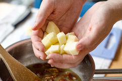 Diced apples. A baker adding diced apples in a bowl of other ingredients for making an apple and pecan nuts pie Stock Photos