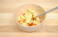 Diced Apples. In a beige bowl with a silver spoon stock images