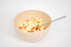 Diced Apples. In a beige bowl with a silver spoon stock photos