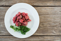 Diced beef and corainder leaves in white plate. Raw diced beef and corainder leaves in white plate against wooden background Royalty Free Stock Photo