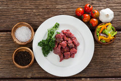 Diced beef and ingredients. Against black background Royalty Free Stock Photography