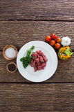 Diced beef and ingredients. Against black background Stock Photos