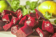 Diced beetrot. Lilac beetroot diced on a white table, near lemon and mint Stock Images