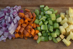 Diced Carrots, Onion, Potato, and Celery. Diced Yukon Gold potato, carrots, celery, and red onions on a cutting board stock image