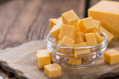 Diced Cheddar (on wood). Diced Cheddar (close-up shot) on rustic wooden background royalty free stock photography
