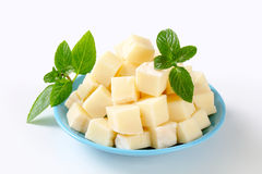 Diced cheese. Heap of diced semi-firm cheese on plate stock photography