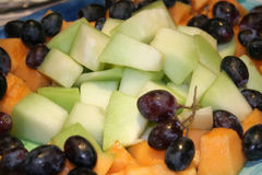 Diced fruit. Salad mixture of honeydew, cantaloupe, grapes, blueberries Stock Photos