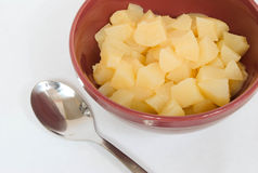 Diced Pears. In a red bowl with a spoon, outside bowl stock photos