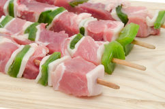 Diced pork kebab skewers on a wooden cutting board Royalty Free Stock Image
