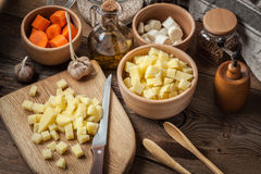 Diced potatoes on a wooden chopping board. Royalty Free Stock Photography