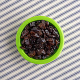 Diced prunes in a green bowl on striped cloth Royalty Free Stock Photo