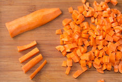 Diced raw carrots on a chopping board. Diced carrot on the kitchen board on background Stock Photography