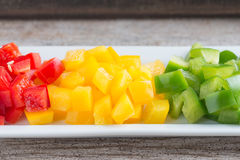 Diced Red, Green & Yellow Pepper. Diced Red, Green & Yellow Pepper together in white plate Royalty Free Stock Image