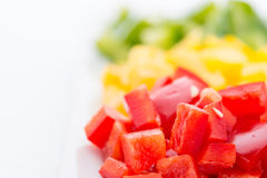 Diced Red, Green & Yellow Pepper. Diced Red, Green & Yellow Pepper together in white plate close up Stock Photo