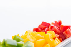 Diced Red, Green & Yellow Pepper. Diced Red, Green & Yellow Pepper together in white plate close up Royalty Free Stock Photos