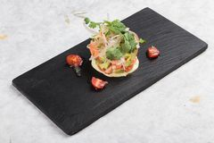 Diced salmon salad with avocado, tomato, onion, chilli, and coriander served in black rectangle stone plate on washi. Stock Images