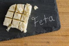 Diced slab of feta cheese on a slate board Royalty Free Stock Photos
