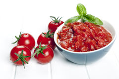 Diced Tomatoes. Diced and whole tomatoes. garnished with basil royalty free stock photography