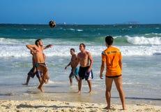6 dicembre 2016 Tre uomini brasiliani che giocano calcio della spiaggia nel moto sui precedenti delle onde alla spiaggia di Copac Immagine Stock