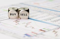 Dices кубики с словами ПРОДАЙТЕ ПОКУПКУ на финансовохозяйственной диаграмме downtrend стоковые фото
