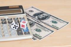 dices на деревянной таблице с долларом США и калькулятором Стоковое Фото