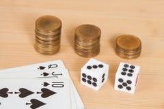 Dices на деревянной таблице с стогом и карточкой coines Стоковые Фото