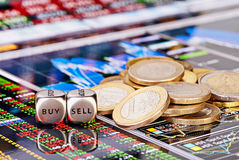 Dices cubes with the words SELL BUY, one-euro coins. And a financial chart as the background. Selective focus royalty free stock images