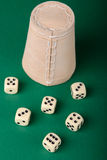 Dices and cup on green background Stock Photos